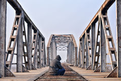 Sad teenager in depression sitting on a bridge at the sunset. Stock Photos