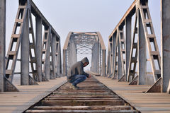 Sad teenager in depression sitting on a bridge at the sunset. Stock Images