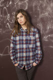 Sad teenager girl in chequered shirt and jeans standing near bro Stock Photography