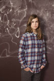 Sad teenager girl in chequered shirt and jeans standing near. Brown wall Royalty Free Stock Images