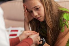Sad teenager girl at counseling - woman professional hands holding and comforting young girl royalty free stock photos