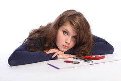 Sad teenager girl fed up with maths homework. Sad and fed up teenager girl lying on floor doing her maths homework with a book, pen and calculator. Girl has long stock image