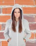 Sad teenager girl with gray sweatshirt. And brick wall background Stock Photos