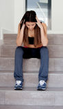 Sad teenager girl sitting on the stairs Stock Photo