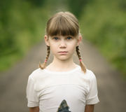 sad teenager girl with two braids standing on rural road Royalty Free Stock Photos