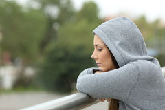 Sad teenager looking down in a balcony. Side view of a sad single teenager looking down in a balcony of her house in a rainy day Royalty Free Stock Photography