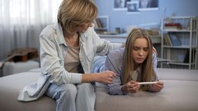 Sad teenager looking at positive pregnancy test, mother supporting daughter. Stock photo royalty free stock photography