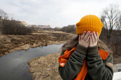 Sad teenager in orange knitten hat and scarf closed her face by hands. Stand alone near the scorched field. Spring time Stock Photo