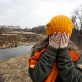 Sad teenager in orange knitten hat. And scarf closed her face by hands, stand alone near the scorched field. Spring time Stock Photo