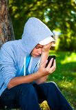 Sad Teenager outdoor. Sad Teenager with Cellphone in the Summer Park Royalty Free Stock Photography