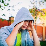 Sad Teenager outdoor. Filtered Photo of Sad Teenager sit on the City Street Royalty Free Stock Images