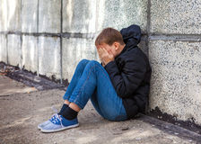 Sad Teenager outdoor. Sad Kid sit by the Wall on the Street stock image