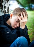 Sad Teenager outdoor. Sad Teenager sit under Tree in the Park Royalty Free Stock Photo