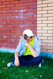 Sad Teenager outdoor. Sad Teenager sit by the Brick Wall outdoor Royalty Free Stock Photo