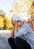 Sad Teenager outdoor. Sad Teenager sit on the City Street royalty free stock photography