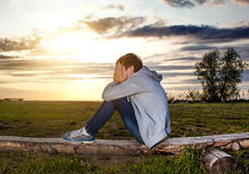 Sad Teenager outdoor. Sad Teenager sit on the Log on the Sunset Background royalty free stock photography