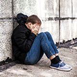 Sad Teenager outdoor. Sad Teenager sit by the Wall on the Street stock image
