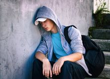 Sad Teenager outdoor. Toned Photo of Sad Teenager sit on the Street Royalty Free Stock Photo