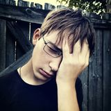 Sad Teenager outdoor. Toned Photo of Sad Teenager on the Wooden Wall Background stock photography