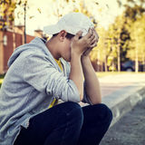 Sad Teenager outdoor. Toned Photo of Sad Teenager sit on the City Street royalty free stock photography