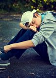 Sad Teenager outdoor. Toned Photo of Sad Teenager sit on the Ground outdoor Royalty Free Stock Images