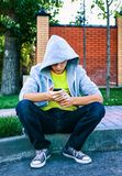 Sad Teenager outdoor. Sad Teenager with a Phone sit on the City Street Royalty Free Stock Photo
