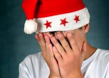 Sad Teenager in Santa Hat Royalty Free Stock Image