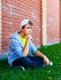 Sad Teenager outdoor. Sad Teenager sit by the Brick Wall outdoor Royalty Free Stock Image