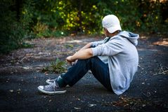 Sad Teenager outdoor. Sad Teenager sit on the Ground outdoor Royalty Free Stock Image