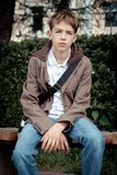 Sad teenager sitting on bench in park Royalty Free Stock Photo
