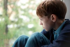 Sad teenager sitting on window stock images