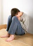 Sad Teenager on Sofa. Sad Teenager on the Sofa hide the Face and Crying Royalty Free Stock Photography
