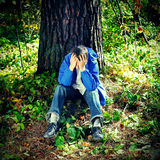 Sad Teenager. Sorrowful Teenager sitting in the Forest royalty free stock image