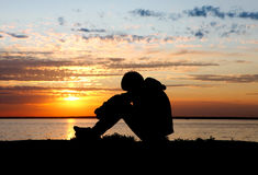 Sad Teenager at Sunset. Sad Teenager Silhouette at the Sunset Background royalty free stock images