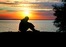 Sad Teenager at Sunset. Sad Teenager Silhouette at the Sunset Background Stock Photography