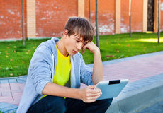 Sad Teenager with Tablet. Computer on the Street stock photo