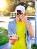 Sad Teenager with Tablet. Troubled Teenager with Tablet Computer on the Street royalty free stock photo