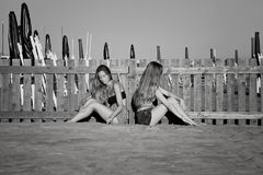 Sad teenagers in silence on the beach not talking after fight black and white. Angry girls after fight on beach stock images