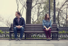Sad teens sitting at the bench at the park Royalty Free Stock Image