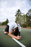 Sad tennis player after defeat. A sad asian tennis player kneeling down in disappointment after defeat stock images