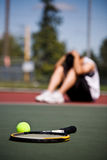 Sad tennis player after defeat. A sad male tennis player sitting down in disappointment after defeat royalty free stock image