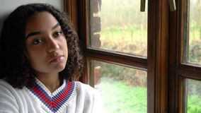 Sad then happy biracial beautiful mixed race African American girl teenager young woman sitting by a window stock footage
