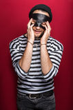 Sad thief with handcuffs. Portrait on red background Stock Photography