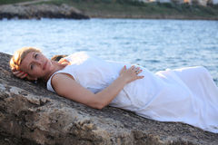 Sad and thinking pregnant woman on the rock Stock Images