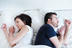 Sad and thoughtful couple after arguing lying in bed Stock Photography