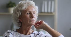 Sad thoughtful mature old adult woman looking away feeling depressed