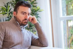 Sad and thoughtful portrait of man alone at home royalty free stock images