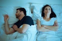 Sad and thoughtful woman awake while husband is sleeping in bed. Sad and thoughtful women awake while husband is sleeping in the bed stock image