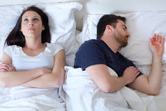 Sad and thoughtful woman awake while husband is sleeping in bed Royalty Free Stock Photography