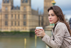 Sad Thoughtful Woman Drinking Coffee in London by Big Ben. Beautiful sad, depressed or thoughtful young woman in London on Westminster Bridge over the River Royalty Free Stock Photo